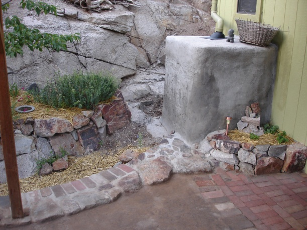 """ALL the roof water descends on this one corner.  Whatever overflows the tank is directed alongside the swale (""""low place"""") around the patio alongside the fruit trees!"""